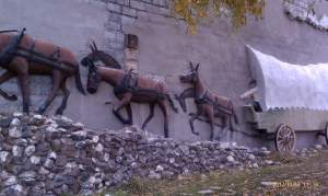 Relief sculpture on wall depicts old west scene.