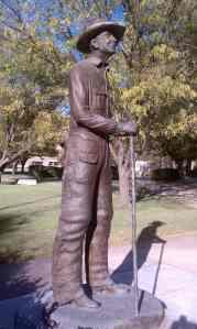 Bronze cowboy stands tall.