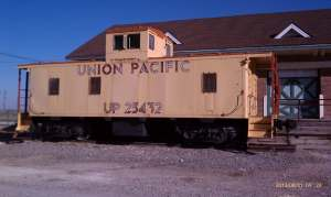 An old yellow caboose at the train depot.