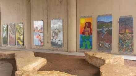 A gallery of fine art outside underneath the bridge.